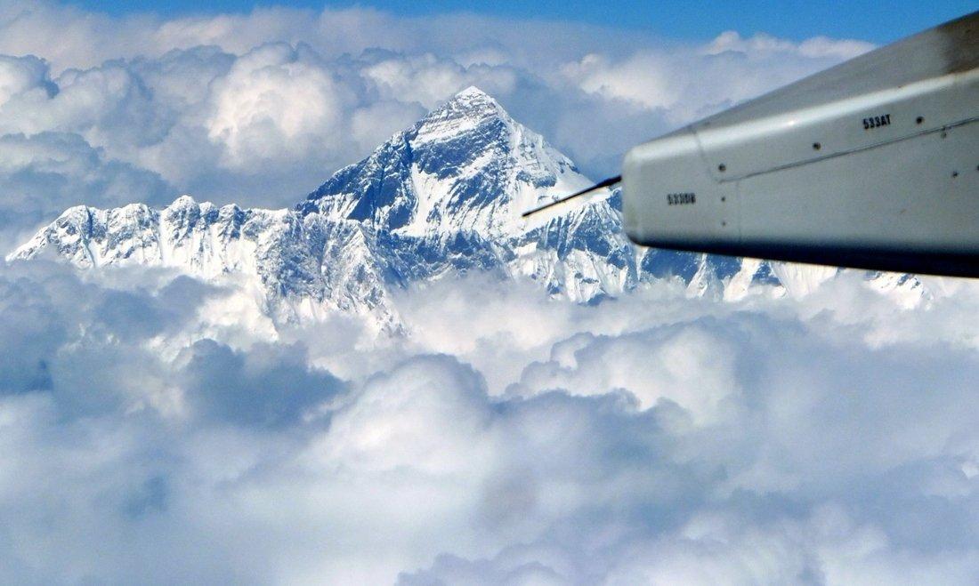 Tourism in Bhutan - The Himalayan mountain range among the clouds as seen from the flight to Bhutan