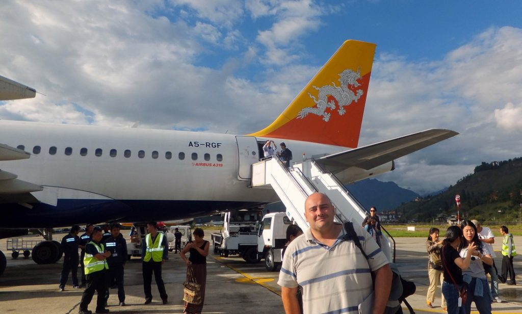 Nikki is at Paro airport near a Druk air plane, - travelling to Bhutan