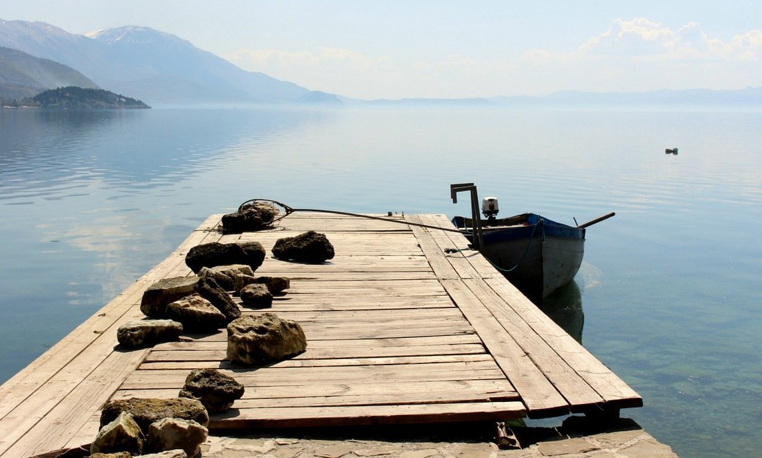 a boat tied to a wooden walkway at the shores of Lake Ohrid, a top amongst our list of places to visit in Macedonia