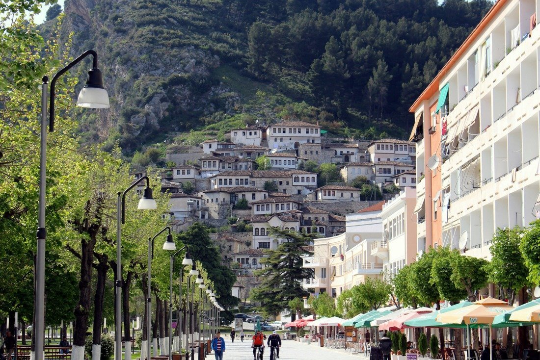 A street in Berat with houses on the hillside behind it