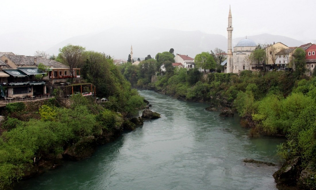 A view of the river running through Mostar with a mosque in the distance