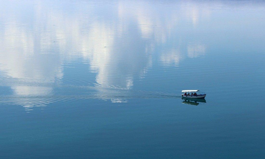 A boat cruising through Lake Ohrid, views from the Church of Sveti Jovan