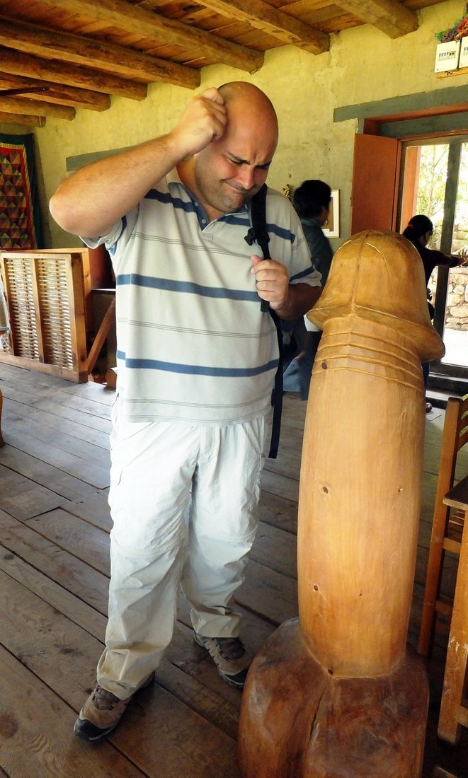 Nikki looking at a giant wooden phallus at a restaurant - places to visit in bhutan