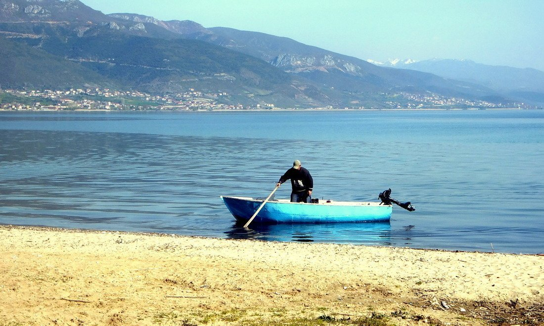A man on a motorboat on the shores of Lake Ohrid in Albania