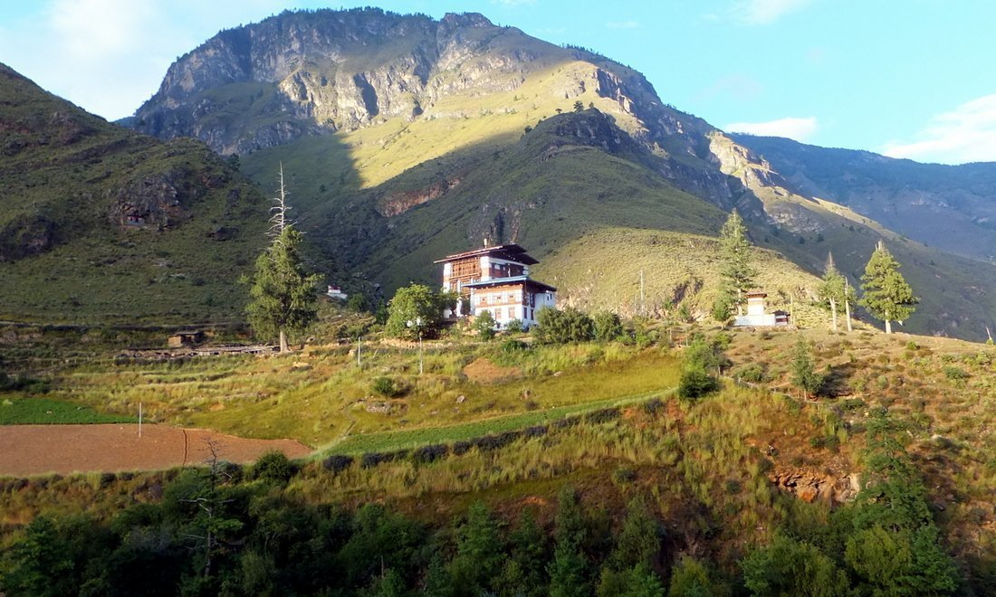 A rural scene of a house set amid hills and forests in Bhutan