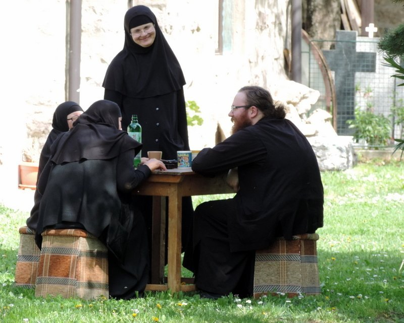 Orthodox nuns and priests have lunch in the monastery grounds near Pristina, kosovo