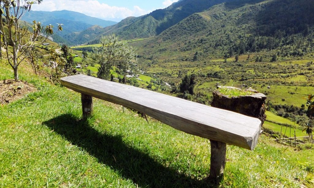 a bench offering a view over a valley in Bhutan - travel to Bhutan