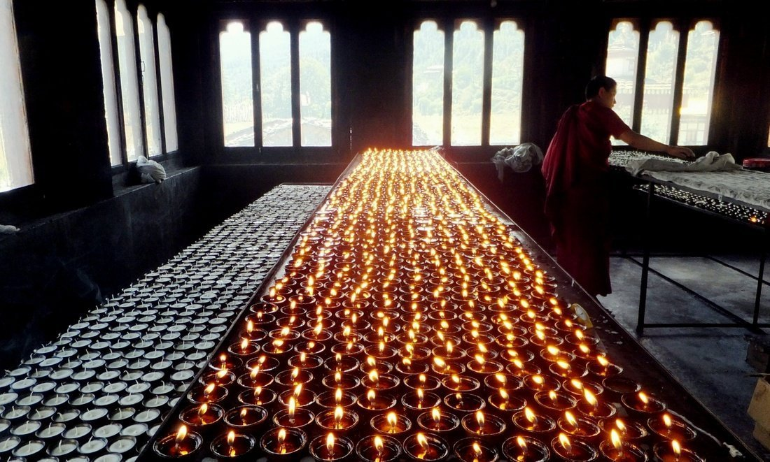A monk lighting butter lamps in a monastery in Bhutan
