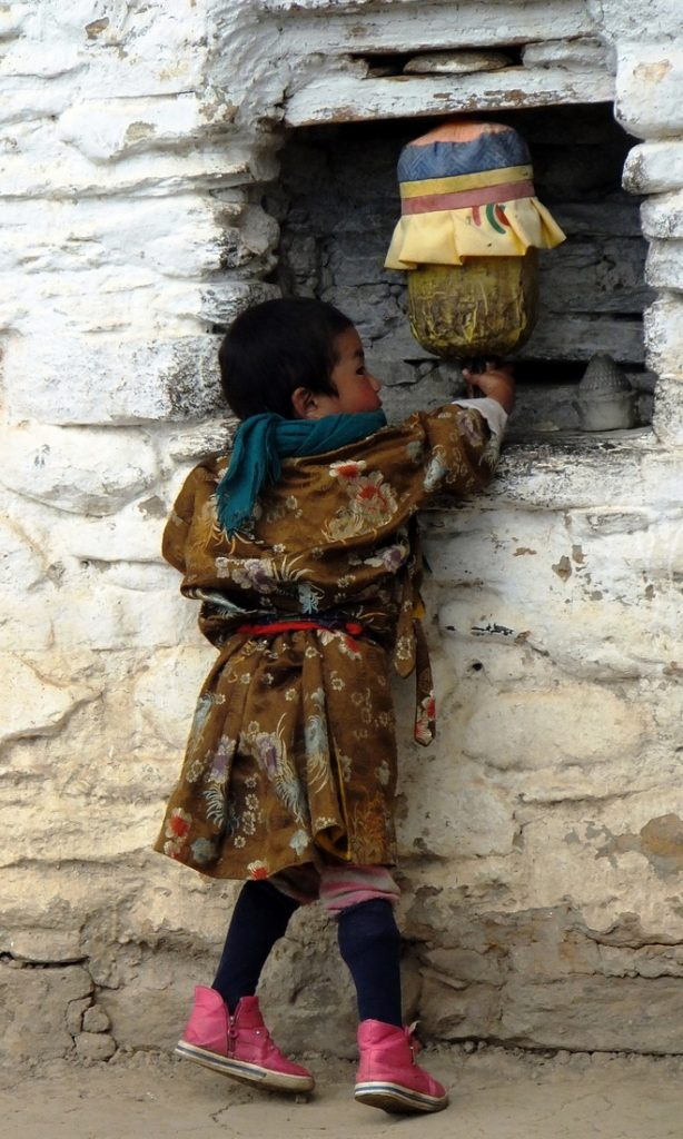travelling to Bhutan - A young Bhutanese child turns a prayer wheel