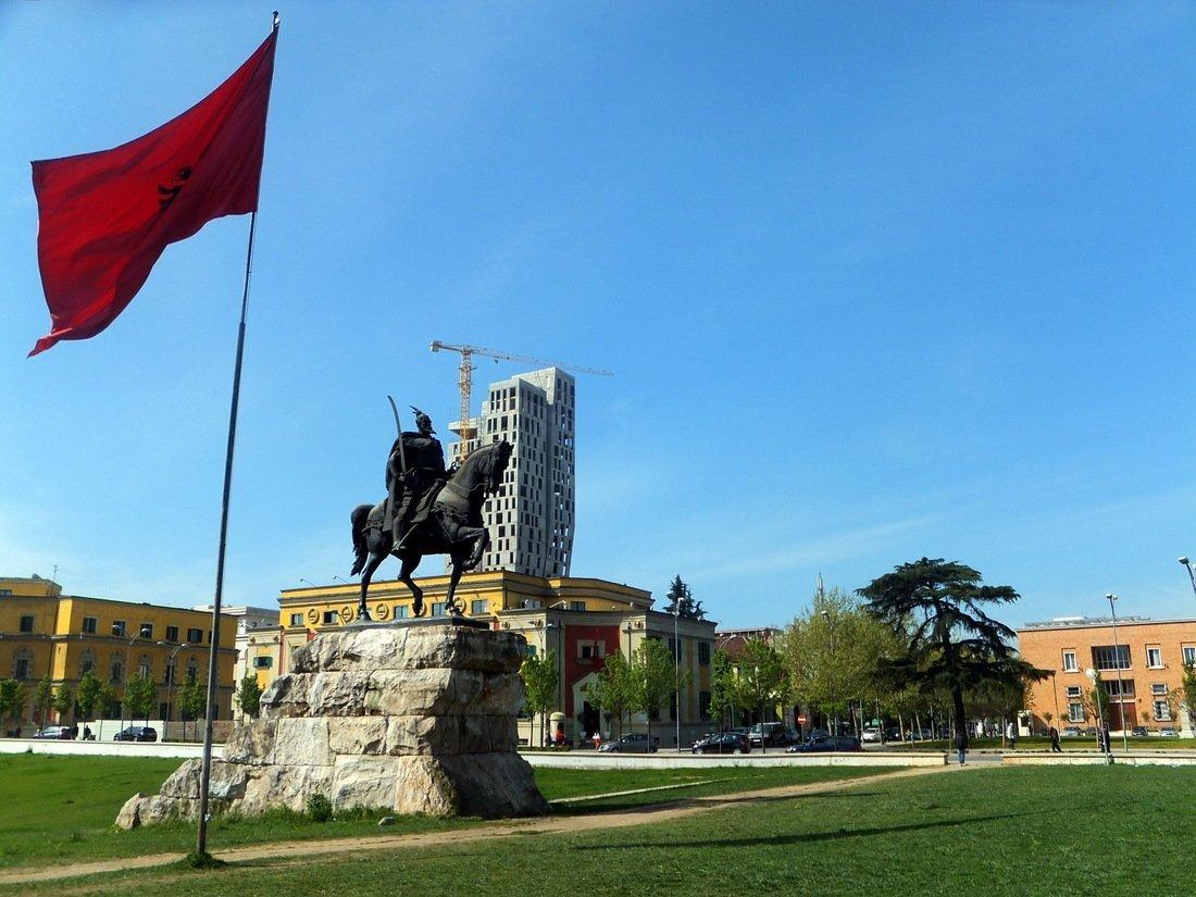 The monument and Albanian flag in Skanderbeg Square in Tirana