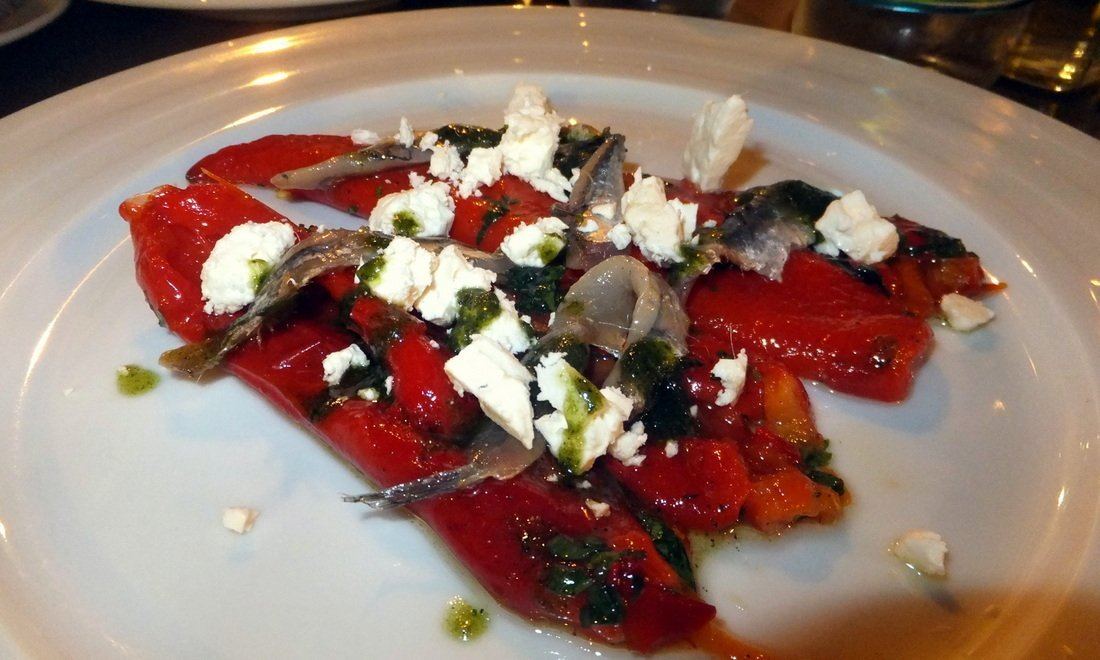 a dish of roast peppers and cheese at a restaurant - Things to do in Tirana