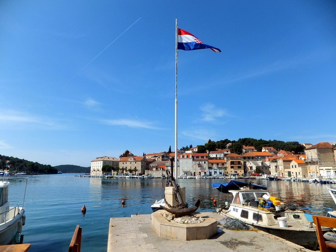 The Croatia flag stands proudly at the Milna harbour on the island of Brač - Day trip to Brač