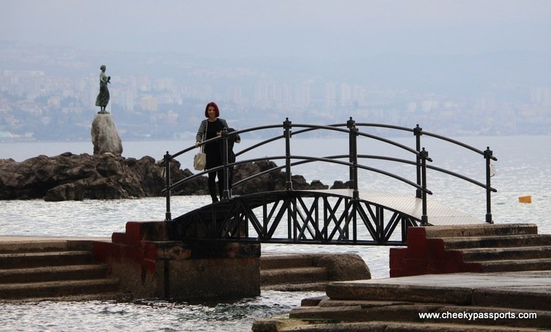 Michelle on a bridge in Opatija with the statue of the maiden in the background - Treasures of Istria