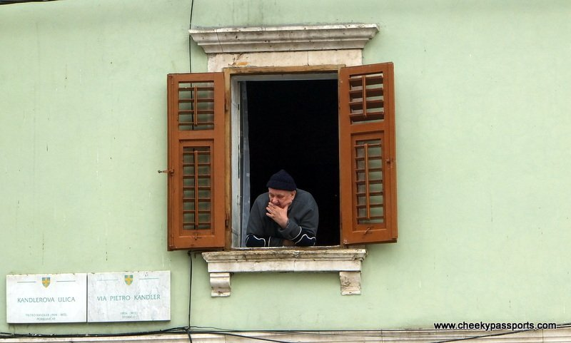 A Pula resident looks out of the window of his home at the street below