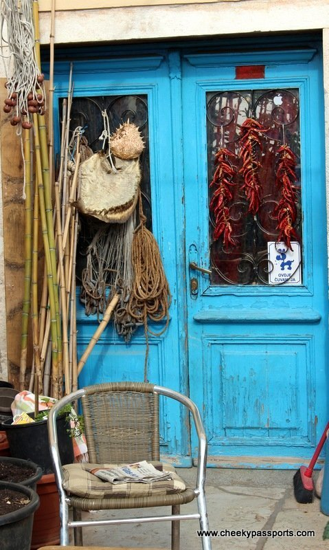 A bright blue door with fishing tackle and bamboo rods - Treasures of Istria