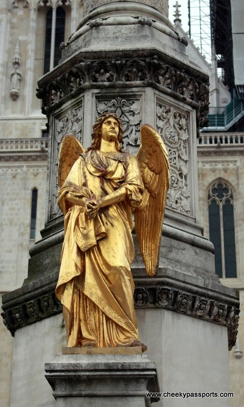 statue of an angel in gold in front of the cathedral