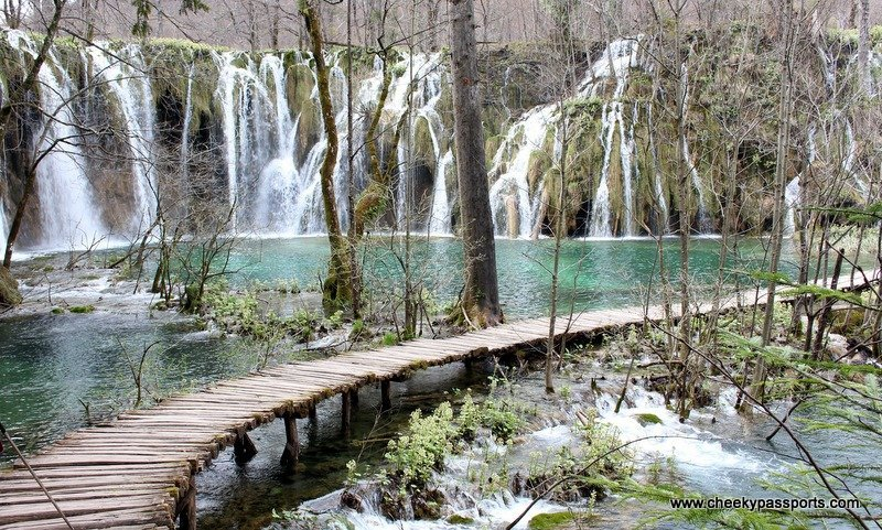 a wooden walkway across the lakes with waterfalls in the background - Plitvice lakes National Park