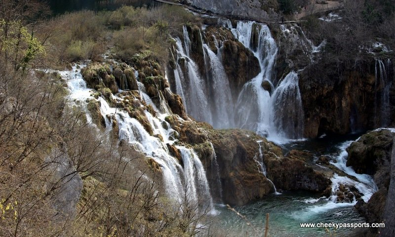 large waterfalls emptying into one of the Plitvice lakes