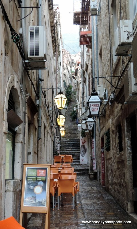 a narrow alleyway with tables and chairs seen during our Dubrovnik visit