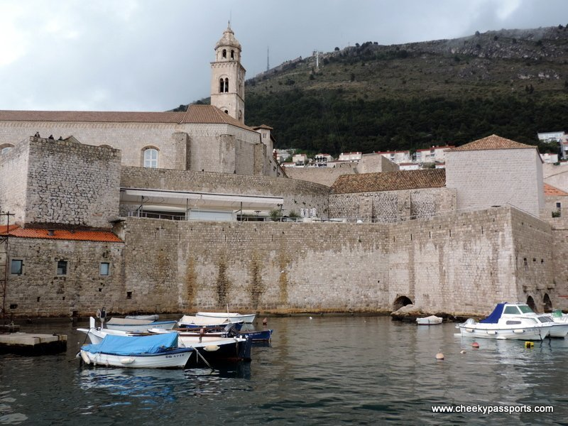 the walls of Dubrovnic surrounded by sea and boats - visit dubrovnik