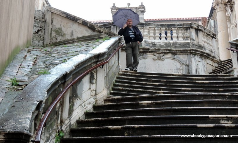 Nikki syanding on a staircase in Dubrovnik holding an umbrella - Visit dubrovnik