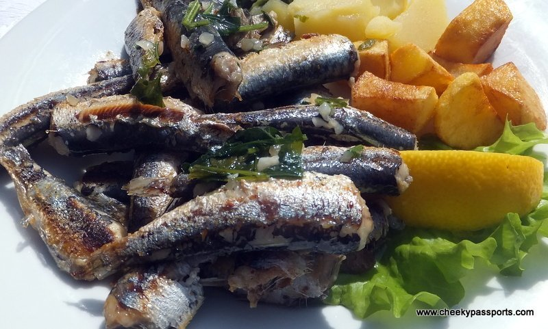 A dish of grilled anchovies and potatoes accompanied by salad