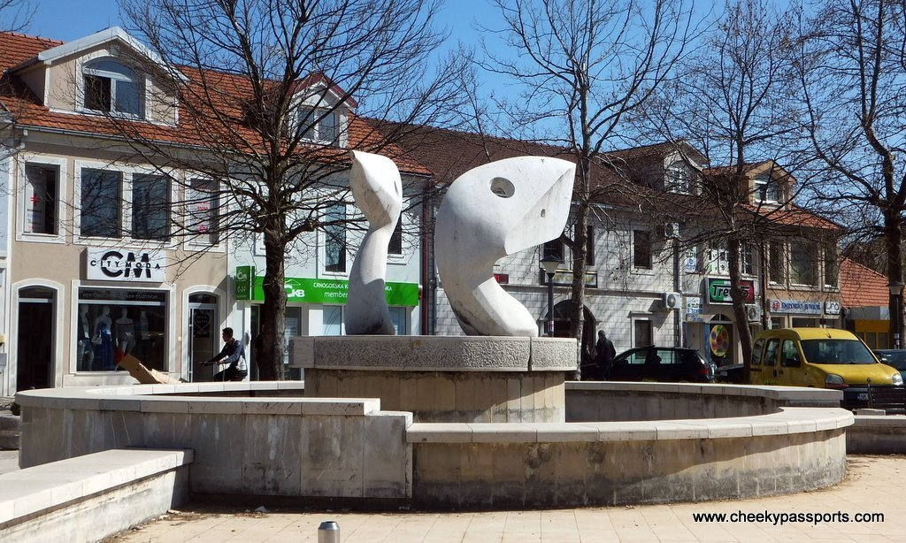 A fountain with a modern art fish sculpture in Niksic square