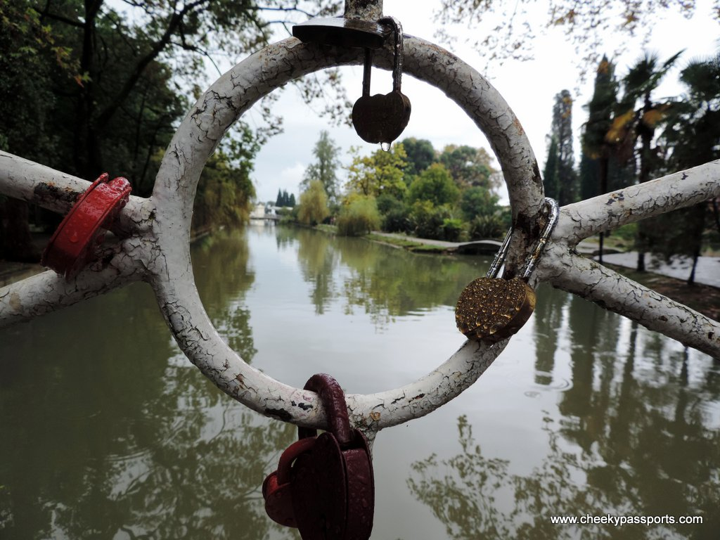 Heart shaped locks adorn a railing on a pond in the a garden - visa to Abkhazia