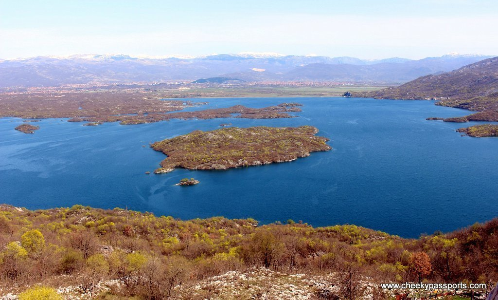 A bright blue lake with little islands with the town of Niksic in the distance