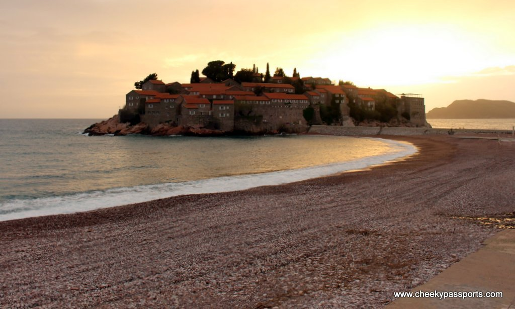 Sveti Stefan on a little island separated from the mainland by a sand bar during sunset, a gem in coastal Montenegro and a good reason to visit Montenegro