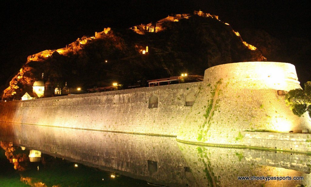 The old town walls of Kotor are lit up by night - a top reason to visit Montenegro
