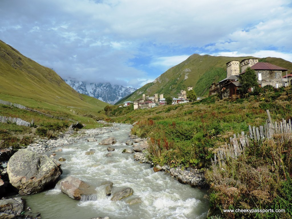 A river runs through Ushguli with a snowy mountain in the background - things to do in georgia, europe