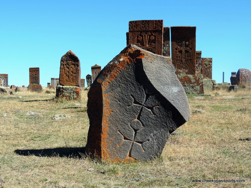 A khachkar depicting a carved crosses surrounded by other khachkars at Noratus cemetery
