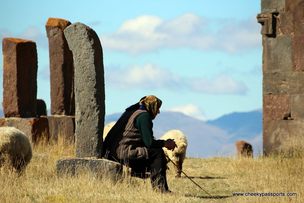 A shepherdess sits on a khachkar as she watches her sheep graze in the cemetery, amongst the top places to visit in Armenia