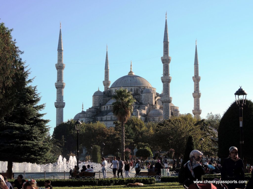 The Blue Mosque with a park and fountain right in front of it to visit during a layover in Istanbul