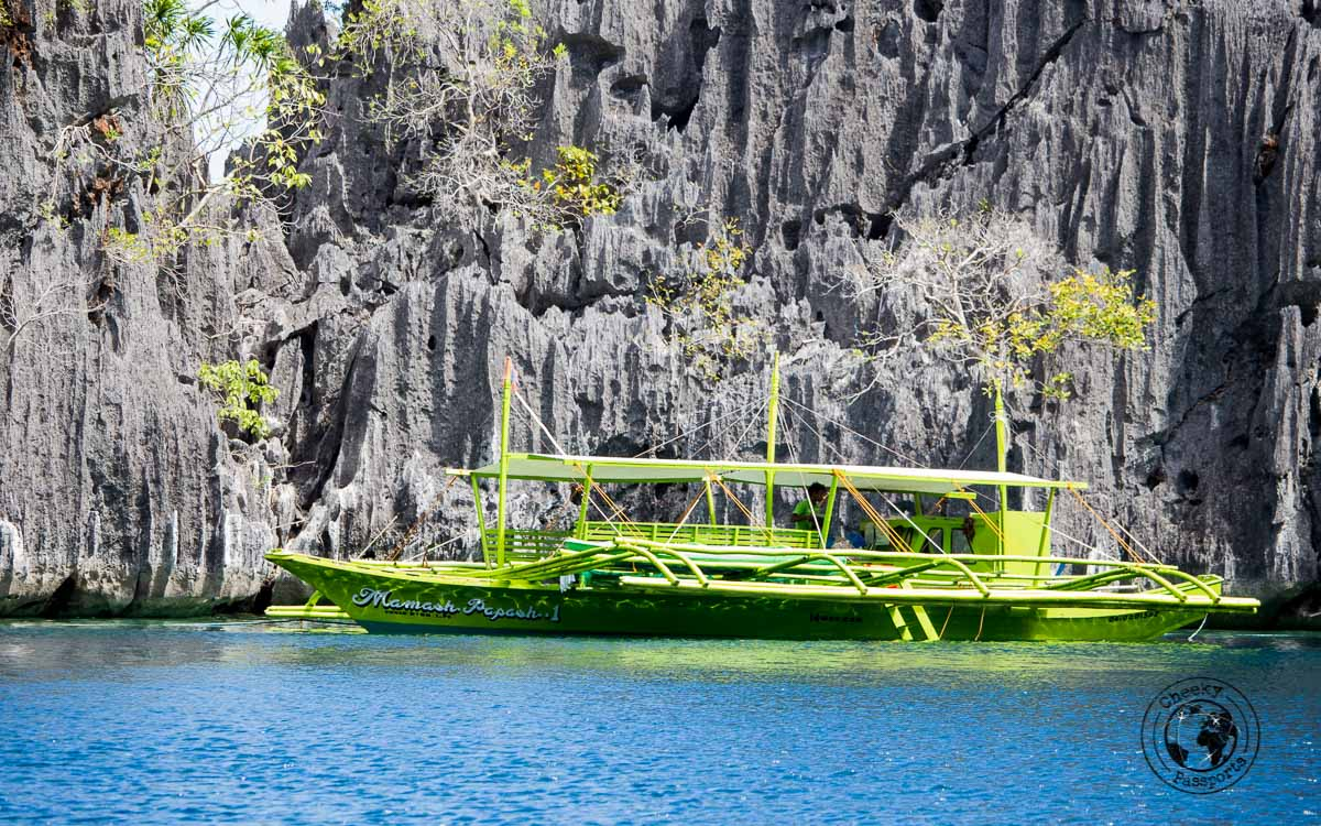 Highlights of Coron - beautiful rock formations with green boat (banka) over a blue sea