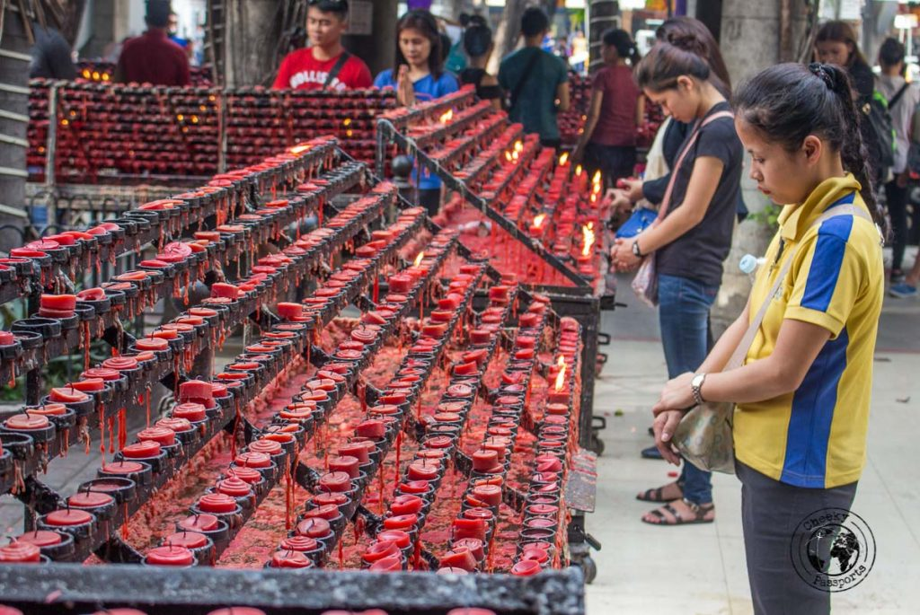 Cebu city walking tour - prayers around red candles at the Basilica minor del santo nino