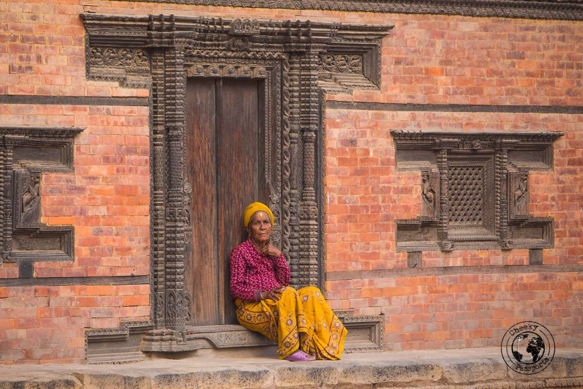 Woman resting on carved door at the Bhaktapur Durbar Square, one of the best places to visit in Kathmandu