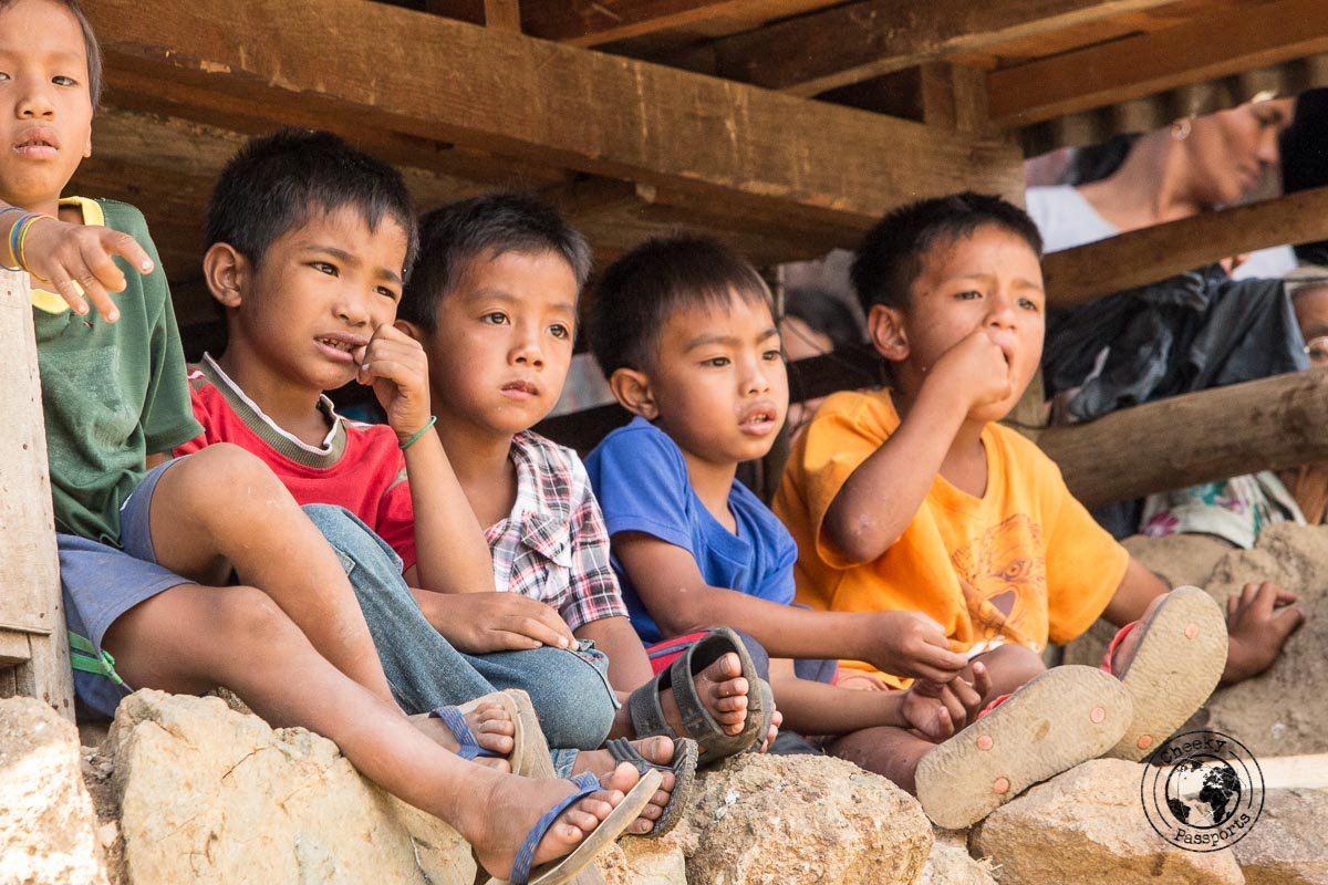 Kalinga Kids taking a vantage point beneath a house structure in Buscalan