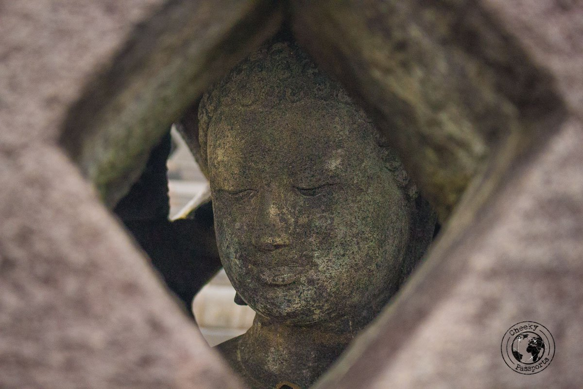 Buddha statue in a bell shaped stupa at Borobodur - Places to visit and things to do in Yogyakarta