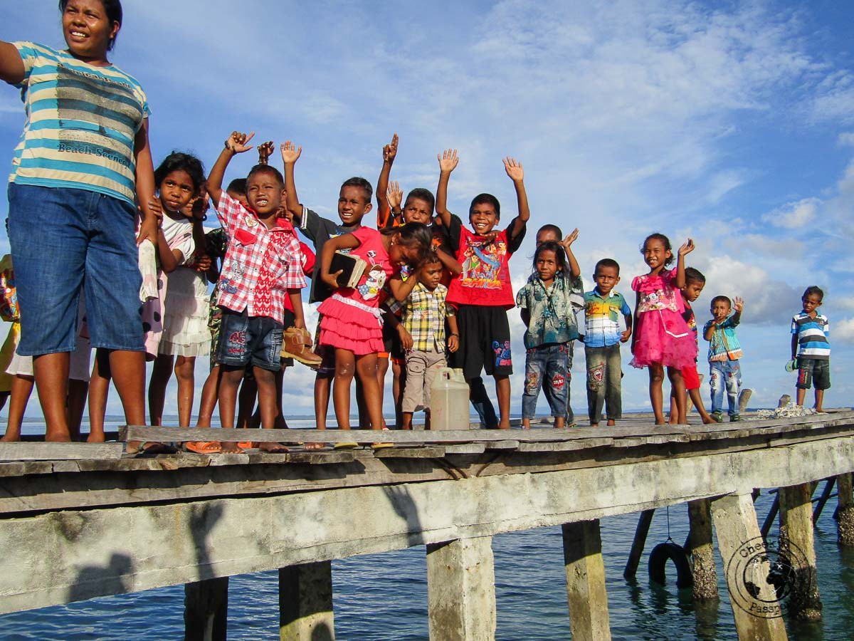 Children waving farewell at a boatload of tourists at Bair island, in the Kei islands