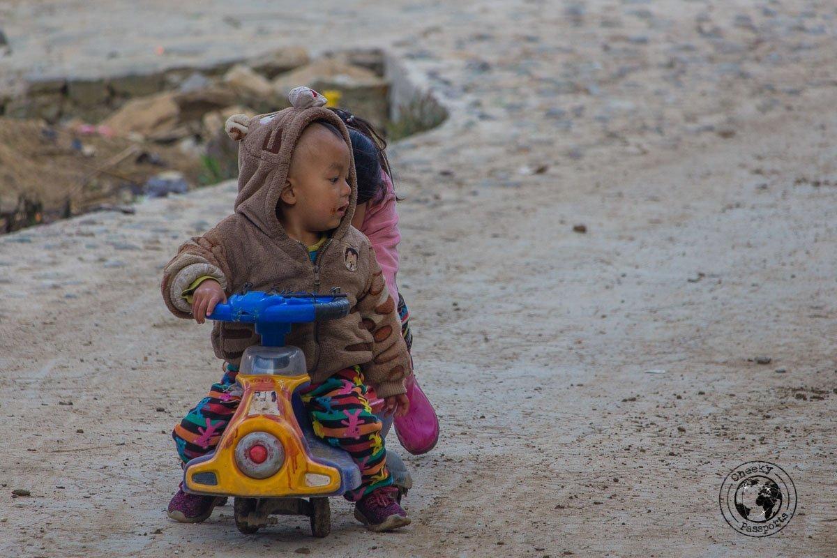 Kids playing at the mushroom village - How to visit the Yuanyang Rice Terraces, Yunnan, China
