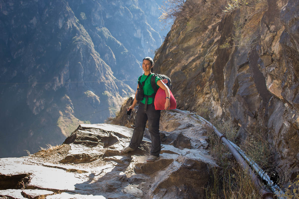 Michelle clutching to her bags along a rough path when hiking tiger leaping gorge