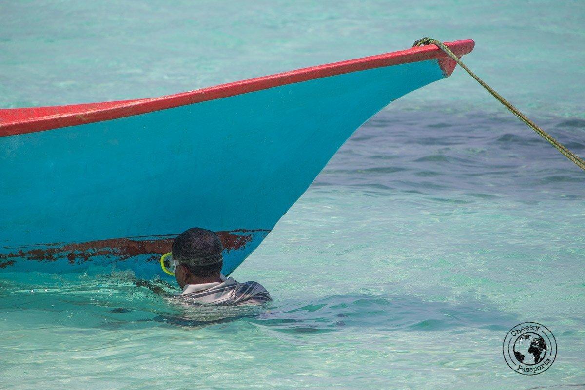Fisherman repairing a boat in the Maldives - Maldives low budget