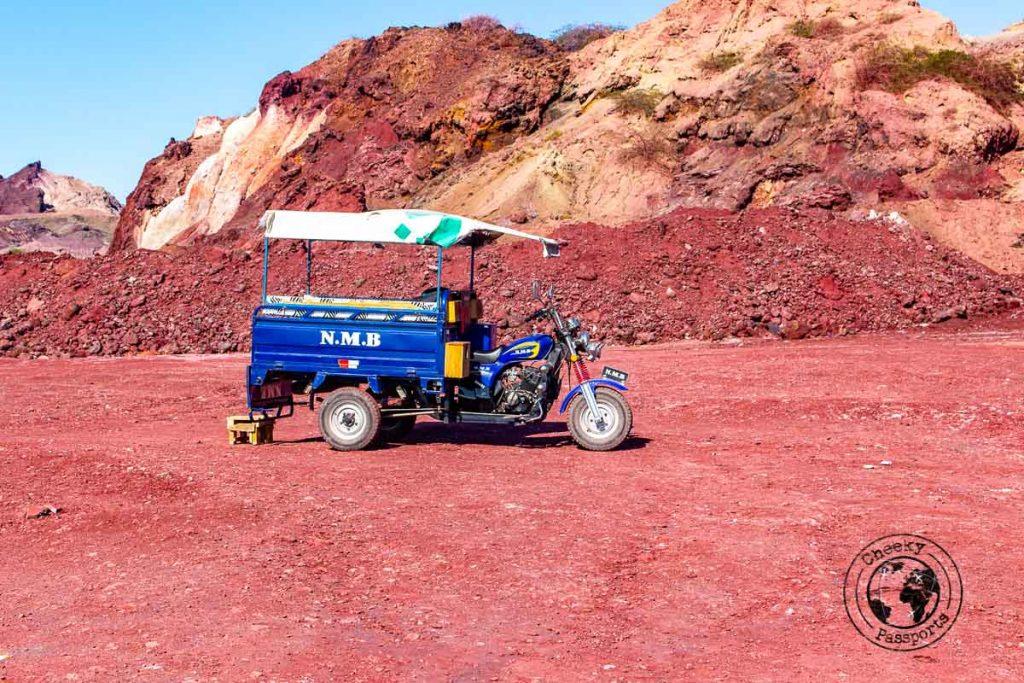 Blue tuk tuk and the red ground of Hormuz island